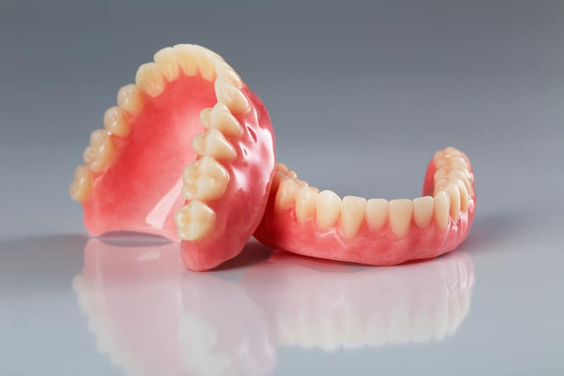 A set of dentures on a shiny background