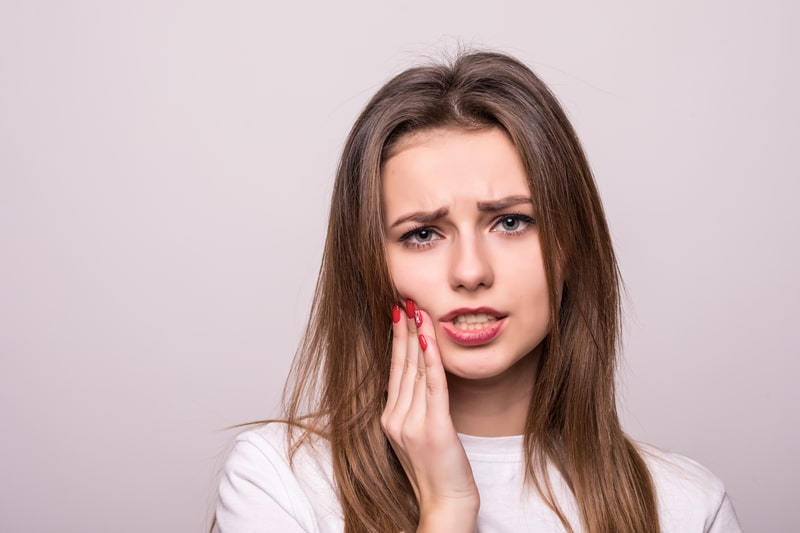 Woman holding hand against jaw in pain