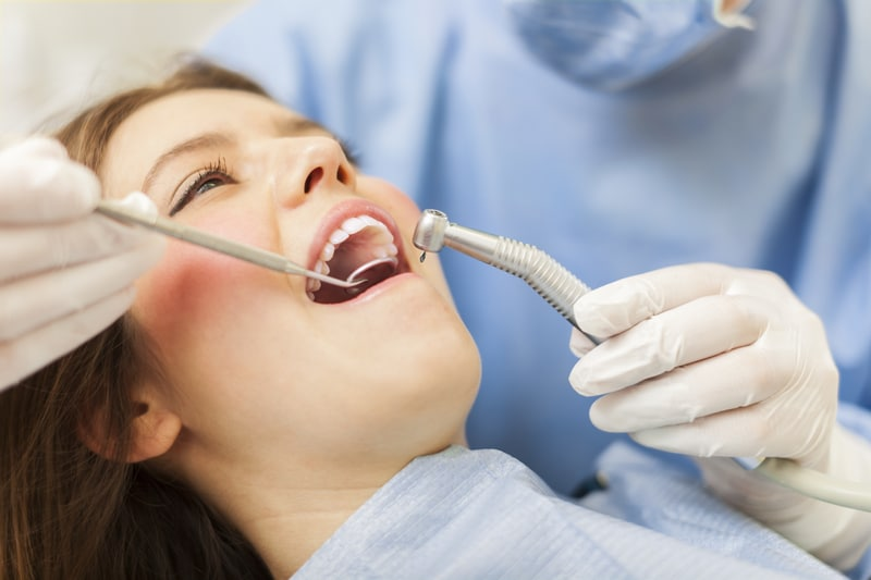 A young adult woman that is smiling as a dentist is about to perform work on her teeth.