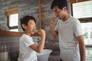 Asian father and son brushing their teeth together in the bathroom.