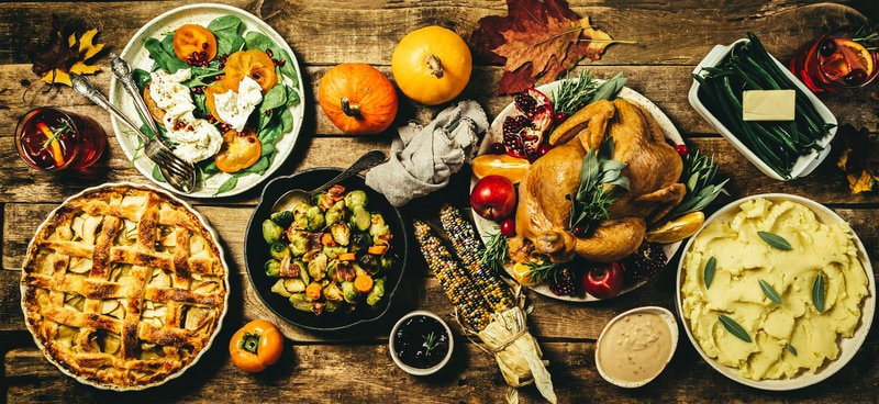 Selection of Thanksgiving foods on a wooden table.