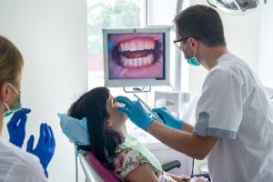 Dentist checking patient's teeth with intraoral camera