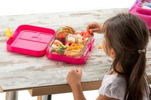 Little girl eating healthy food out of lunchbox