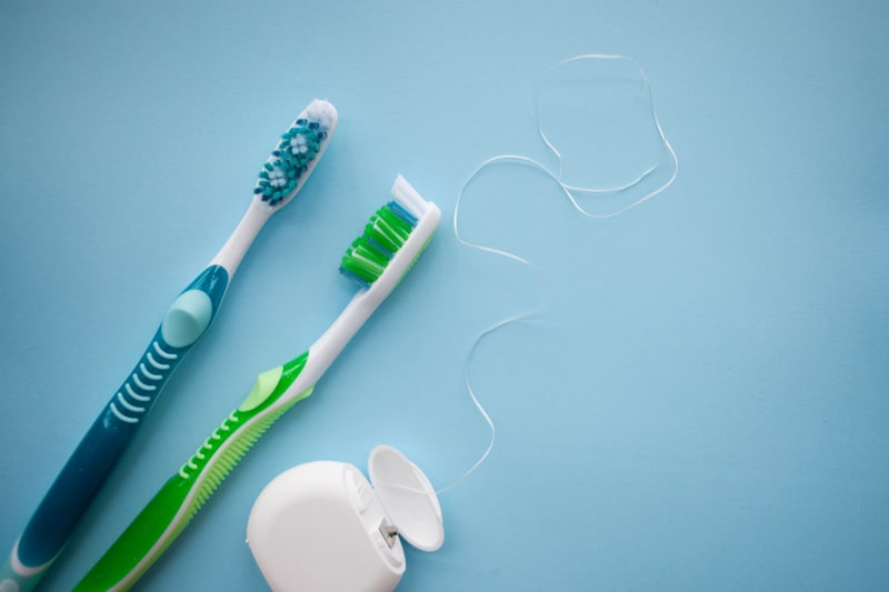 Picture of two toothbrushes and floss