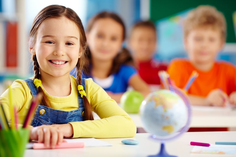 Young girl sitting in school class room with peers all smiling
