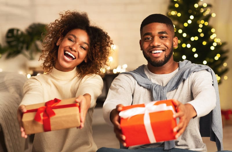 African American couple sitting in front of a Christmas tree smiling at the camera with presents in their hands.