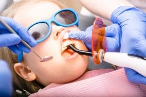 Dentist performing dental filling on a little girl's tooth