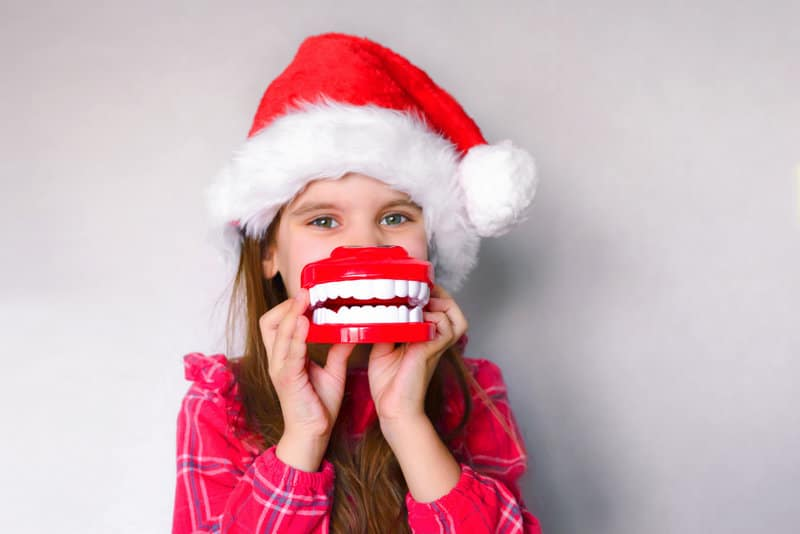 Little girl wearing a santa hat and holding fake teeth in front of her mouth.