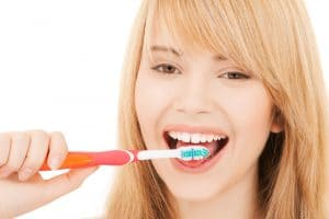 Teenage girl scrubbing tongue with toothbrush